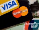中国本土で広く普及する銀聯(右下)と二大国際ブランドのカード(資料)—本紙撮影