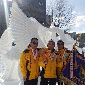 優勝旗を手に作品の前で記念撮影に臨むマカオ代表チームの3人=2月9日、北海道札幌市(写真:MGTO)
