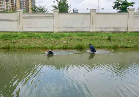 密入境者に扮してキャンパス外周の水路を進むマカオ税関職員=2018年7月9日(写真:澳門海關)