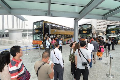 港珠澳大橋のマカオ側と香港側のイミグレーション施設と往来するシャトルバスに乗り込む乗客=2018年10月24日、港珠澳大橋マカオ側イミグレーション施設内(写真:GCS)