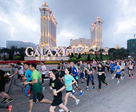 ギャラクシーエンターテイメントグループの旗艦IR(統合型リゾート)施設「ギャラクシーマカオ」前を走る選手ら=2018年12月2日、マカオ・コタイ地区(写真:Galaxy Entertainment Group)