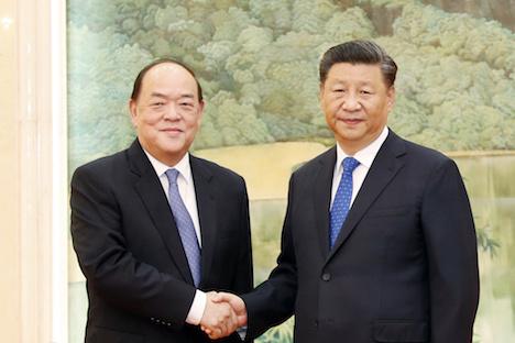 習近平中国国家主席(右)と握手する賀一誠氏(写真:GCS)