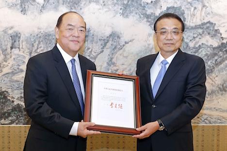 李克強中国国務院総理(右)から任命書を受け取る賀一誠氏(写真:GCS)